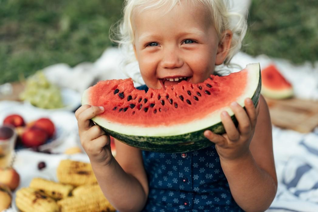copil mănâncă pepene roșu